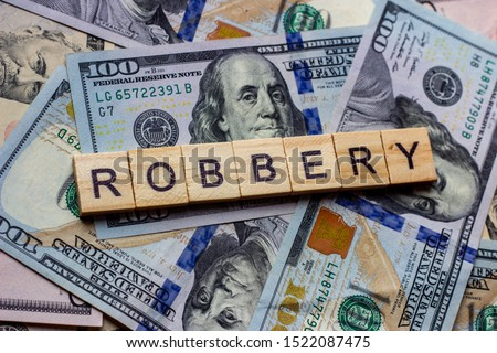 The word robbery on dollar usa background. Theft and stealing money concept ストックフォト ©