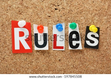 The word Rules in cut out magazine letters on a cork notice board