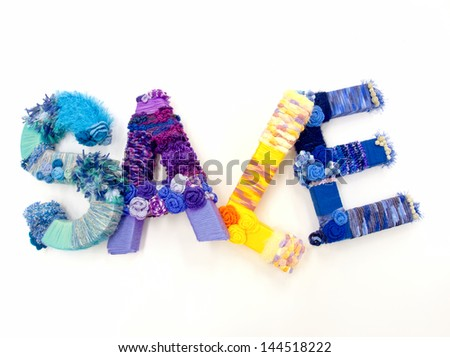 "the word ""sale"" created with brightly colored knitting yard"