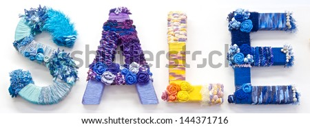 "the word ""sale"" created with brightly coloured knitting yard"