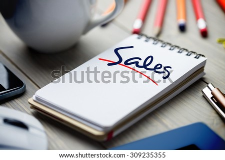 The word sales against notepad on desk