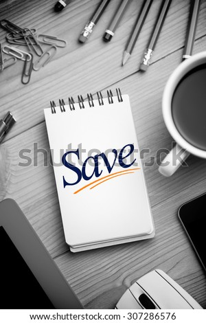 The word save against notepad on desk