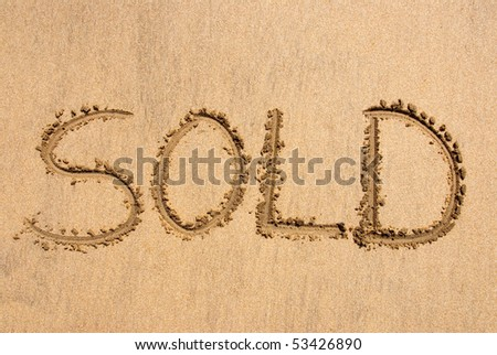 The word SOLD written out on a sandy beach - stock photo