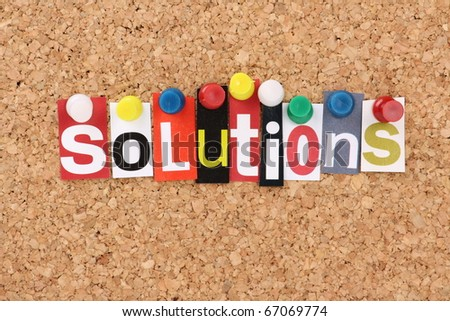 The word Solutions in cut out magazine letters pinned to a cork notice board