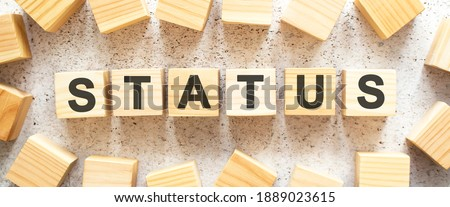 The word STATUS consists of wooden cubes with letters, top view on a light background. Work space. Stock photo ©