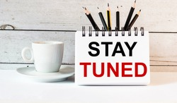 The word STAY TUNED is written in a white notepad near a white cup of coffee on a light background