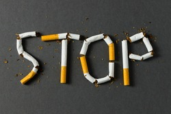 The word stop spelled using cigarettes on black background