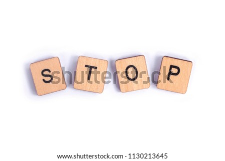 The word STOP, spelt with wooden letter tiles.