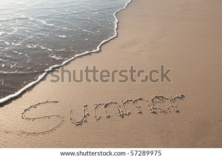 the word summer written in sand