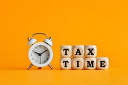 The word tax time written on wooden cubes with an alarm clock on yellow background. Tax payment reminder or annual taxation concept.
