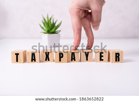 the word taxpayer wooden cubes with burnt letters, debts, gray background top view. Stock photo ©