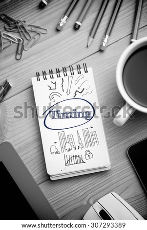 The word timing and business and cityscape against notepad on desk