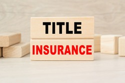 the word TITLE INSURANCE is written on a wooden cubes structure. Cube on a bright background. Can be used for business, marketing, financiaL, INSURANCE concept. Selective focus.