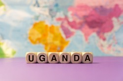 The word Uganda written with wooden dices in front of a purple background and a geographic map