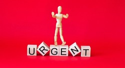 The word URGENT. Wooden cubes with letters isolated on red background with copy space. Conceptual image. Wooden doll