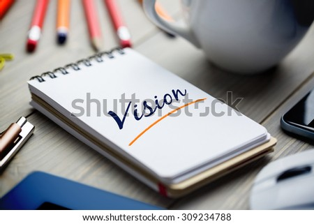 The word vision against notepad on desk