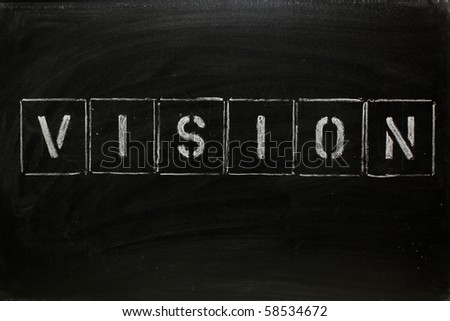 The word VISION in stencil letters on a blackboard