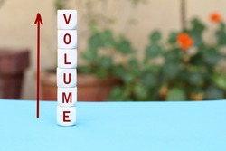 The word volume on stacked cubes with arrow. Increasing music volume or production quantity or capacity in business concept.