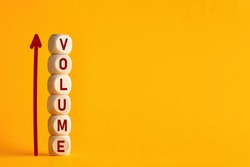 The word volume on stacked wooden cubes with arrow. Increasing music volume or production quantity or capacity in business concept.