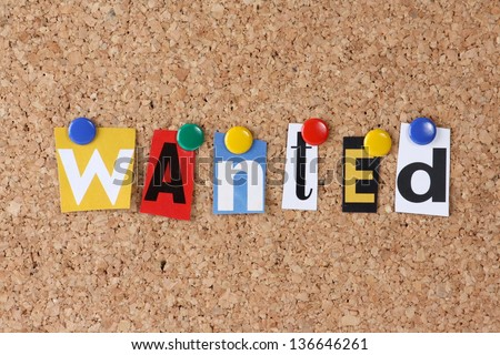 The word Wanted in cut out magazine letters pinned to a cork notice board