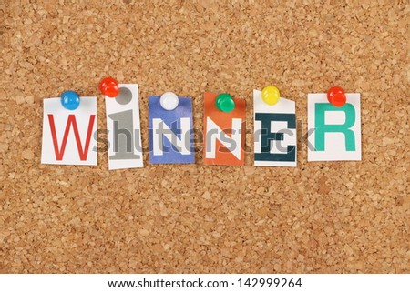The word Winner in cut out magazine letters pinned to a cork notice board We look for winners in competitive sports competition and business