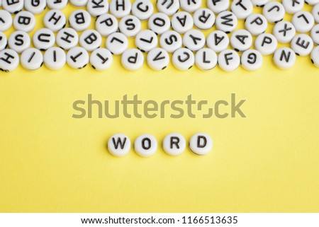 The word WORD made of white plastic blocks on yellow background with many letters on the top #1166513635