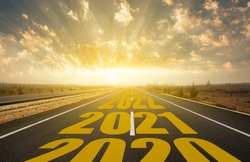 The word 2021 written on highway road in the middle of empty asphalt road at golden sunrise