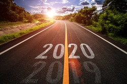 The word 2020 written on highway road in the middle of empty asphalt road at golden sunset and beautiful blue sky. Concept for new year 2020.