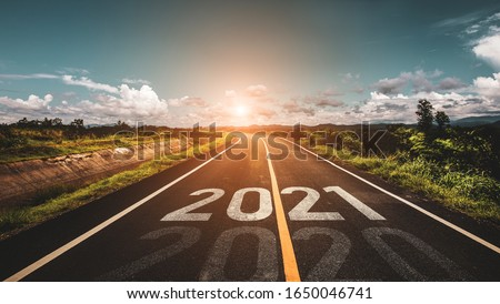 The word 2021 written on highway road in the middle of empty asphalt road at golden sunset and beautiful blue sky. Concept for new year 2021.
