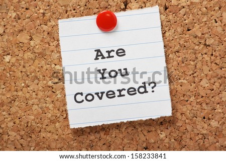 The words Are You Covered typed on a scrap of lined paper and pinned to a cork notice board Asking the question are you insured for your car travel home or other liability