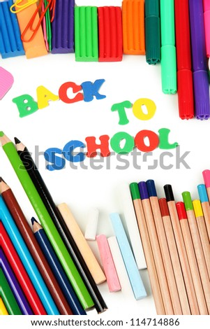 The words 'Back to School' composed of letters with various school supplies close-up isolated on white