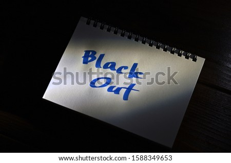 "The words ""Black Out"" written on notebook which is illuminated by light from the gap in diagonal angle."