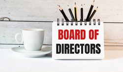 The words BOARD OF DIRECTORS is written in a white notepad near a white cup of coffee on a light background