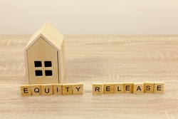 The words equity release in front of a small wooden house