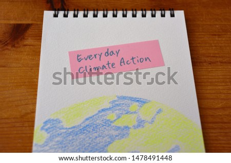 "The words ""Everyday climate action"" written on a slip. And illustration of part of the  earth on sketchbook. It is in the center."