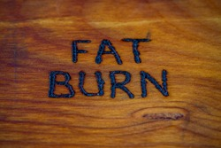 the words fat burn handritten on wooden surface with woodburner