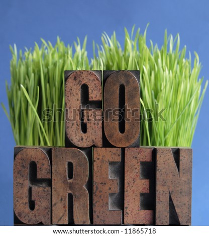 the words 'go green' in letterpress wood letters against fresh green grass