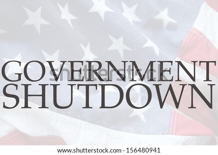 the words government shutdown on an old USA flag