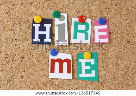 The words Hire Me in cut out magazine letters pinned to a cork notice board as a concept for job hunting and employment