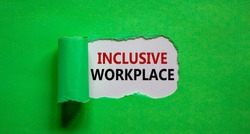 The words 'inclusive workplace' appearing behind torn green paper. Beautiful background. Business and better inclusion concept. Copy space.