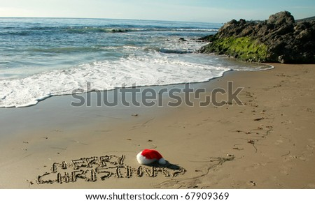 "the words ""Merry Christmas"" written in wet sand with a ""Santa Hat"" on a secluded beach in ""southern california"" with the tide of the pacific ocean and blue sky in the background"