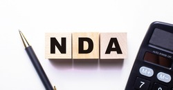The words NDA Non Disclosure Agreements is written on wooden cubes between a pen and a calculator on a light background.
