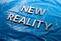 the words new reality laid with white letters over crumpled blue plastic film background - slanted perspective