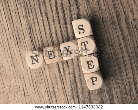 The words Next Step on small wooden dices on a table, close up shot, view from above