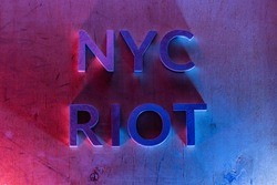 The words NYC riot laid with metal letters on flat plywood surface under red and blue police lights. Concept.