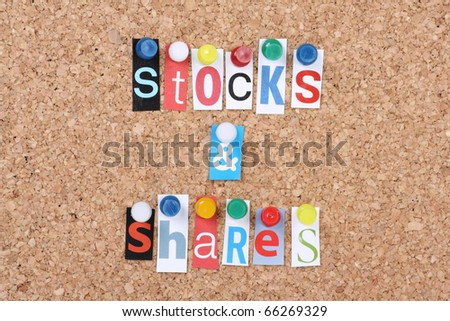 the words stocks and shares in cut out magazine letters pinned to a cork board as