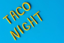 The words TACO NIGHT are made of clay on a blue background, flat lay. USA, Mexican holiday, background with text.