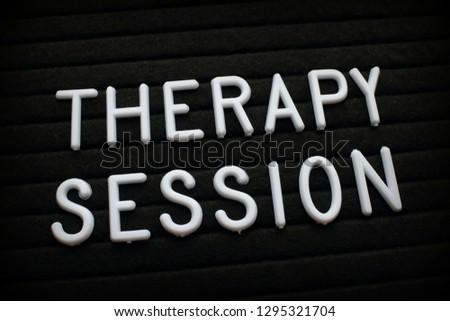The words Therapy Session in white plastic letters on a felt notice board