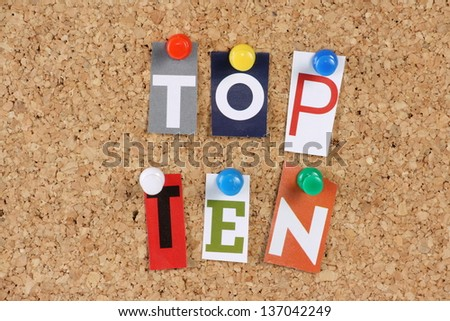The words Top Ten in cut out magazine letters pinned to a cork notice board