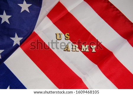 The words US Army written wooden letters on the USA flag background. American military power concept.